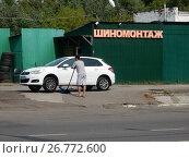 Купить «Автослесарь поднимает автомобиль домкратом. Шиномонтажная мастерская при автостоянке «Лихоборка» на Сигнальном проезде. Район Отрадное. Город Москва», эксклюзивное фото № 26772600, снято 19 августа 2017 г. (c) lana1501 / Фотобанк Лори