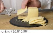 Купить «Cutting of cheese into thin slices by means of a cheese slicer on a round chopping board from black slate», видеоролик № 26810904, снято 23 июля 2017 г. (c) Anatoly Timofeev / Фотобанк Лори