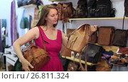 happy young blonde woman in shop chooses hand bags. Стоковое видео, видеограф Яков Филимонов / Фотобанк Лори