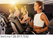 Slender athletic girls running on treadmill in fitness club. Стоковое фото, фотограф Яков Филимонов / Фотобанк Лори
