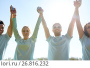 group of happy volunteers holding hands outdoors. Стоковое фото, фотограф Syda Productions / Фотобанк Лори
