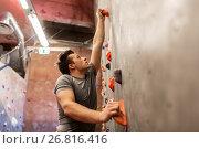 Купить «young man exercising at indoor climbing gym», фото № 26816416, снято 2 марта 2017 г. (c) Syda Productions / Фотобанк Лори