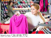 Купить «Girl choosing a sporty jacket», фото № 26818772, снято 25 апреля 2019 г. (c) Яков Филимонов / Фотобанк Лори