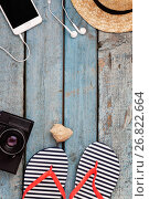 Купить «Still life of different items for relaxing on the beach, rubber flip-flops, hat, camera, phone, sunglasses, headset on a wooden blue background. Concept of a youth trip, rest on the beach with perfumed gadgets», фото № 26822664, снято 5 июля 2017 г. (c) Tetiana Chugunova / Фотобанк Лори