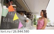 Купить «young woman ordering meal at food truck», видеоролик № 26844580, снято 23 мая 2019 г. (c) Syda Productions / Фотобанк Лори