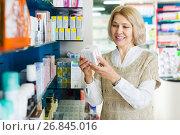 Купить «Female near counter in pharmacy», фото № 26845016, снято 22 октября 2018 г. (c) Яков Филимонов / Фотобанк Лори