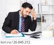 Купить «Spanish male worker is having complicated issue with project», фото № 26845212, снято 29 июля 2017 г. (c) Яков Филимонов / Фотобанк Лори