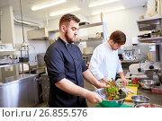 Купить «chef and cook cooking food at restaurant kitchen», фото № 26855576, снято 2 апреля 2017 г. (c) Syda Productions / Фотобанк Лори