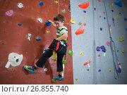Купить «Boy practicing rock climbing in fitness studio», фото № 26855740, снято 10 мая 2017 г. (c) Wavebreak Media / Фотобанк Лори