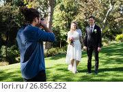 Купить «Photographer taking photo of newly married couple», фото № 26856252, снято 2 мая 2017 г. (c) Wavebreak Media / Фотобанк Лори