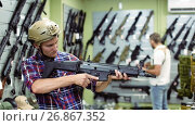 Купить «Young guy in military equipment with gun in airsoft shop», видеоролик № 26867352, снято 14 июля 2017 г. (c) Яков Филимонов / Фотобанк Лори