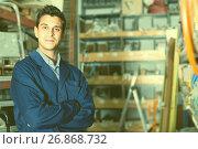 Portrait of male seller in uniform standing near shelving. Стоковое фото, фотограф Яков Филимонов / Фотобанк Лори
