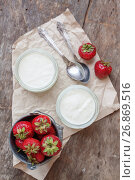 Купить «Yogurt with strawberries in a glass and a bucket with fresh strawberries on a wooden background, top view», фото № 26869516, снято 18 июня 2017 г. (c) Tetiana Chugunova / Фотобанк Лори