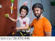Купить «Trainer assisting boy in rock climbing at fitness studio», фото № 26870448, снято 10 мая 2017 г. (c) Wavebreak Media / Фотобанк Лори