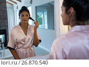 Купить «Woman applying blush with reflection on mirror», фото № 26870540, снято 25 мая 2017 г. (c) Wavebreak Media / Фотобанк Лори