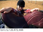 Close-up of girl adjusting saddle on horse. Стоковое фото, агентство Wavebreak Media / Фотобанк Лори