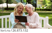 Купить «daughter with tablet pc and senior mother at park», видеоролик № 26873132, снято 20 августа 2019 г. (c) Syda Productions / Фотобанк Лори