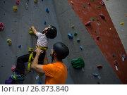 Купить «Trainer assisting boy in rock climbing», фото № 26873840, снято 10 мая 2017 г. (c) Wavebreak Media / Фотобанк Лори