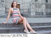 Купить «Cheerful female is playfully posing sitting», фото № 26874792, снято 30 июля 2017 г. (c) Яков Филимонов / Фотобанк Лори