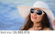 Купить «Beautiful young woman in glasses sunbathing on the beach against the sea», видеоролик № 26880816, снято 5 сентября 2017 г. (c) Happy Letters / Фотобанк Лори