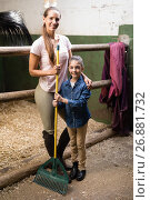 Купить «Portrait of female jockey with sister holding rake», фото № 26881732, снято 3 мая 2017 г. (c) Wavebreak Media / Фотобанк Лори
