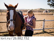 Young woman fastening saddle on horse. Стоковое фото, агентство Wavebreak Media / Фотобанк Лори