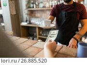 Купить «man or bartender serving customer at coffee shop», фото № 26885520, снято 8 декабря 2016 г. (c) Syda Productions / Фотобанк Лори