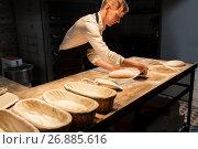 Купить «chef or baker making dough at bakery», фото № 26885616, снято 15 мая 2017 г. (c) Syda Productions / Фотобанк Лори