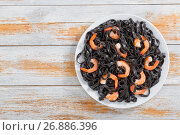 Купить «Cuttlefish ink pasta with prawns on white plate», фото № 26886396, снято 29 ноября 2016 г. (c) Oksana Zh / Фотобанк Лори