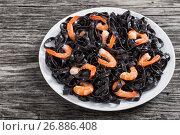 Купить «tasty Cuttlefish ink black noodles with prawns on white dish», фото № 26886408, снято 29 ноября 2016 г. (c) Oksana Zh / Фотобанк Лори