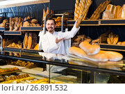 Купить «Male shop assistant demonstrating delicious loaves of bread in bakery», фото № 26891532, снято 26 января 2017 г. (c) Яков Филимонов / Фотобанк Лори