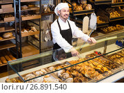 Купить «Satisfied male pastry maker demonstrating croissant», фото № 26891540, снято 26 января 2017 г. (c) Яков Филимонов / Фотобанк Лори