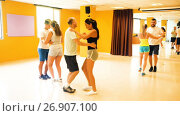 Купить «Smiling adults dancing bachata together in dance studio», видеоролик № 26907100, снято 6 июля 2017 г. (c) Яков Филимонов / Фотобанк Лори