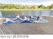 group of people making yoga exercises outdoors. Стоковое фото, фотограф Syda Productions / Фотобанк Лори