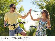 Купить «happy couple with bicycles making high five», фото № 26910124, снято 23 июля 2017 г. (c) Syda Productions / Фотобанк Лори