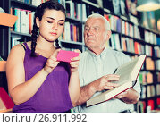 Купить «Old man is choosing book while girl chatting by phone in bookstore.», фото № 26911992, снято 28 июня 2017 г. (c) Яков Филимонов / Фотобанк Лори