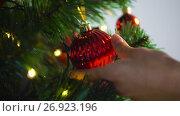 Купить «hand decorating christmas tree with ball», видеоролик № 26923196, снято 9 сентября 2017 г. (c) Syda Productions / Фотобанк Лори