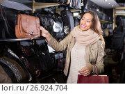 Купить «Happy female customer choosing new handbag», фото № 26924704, снято 19 января 2019 г. (c) Яков Филимонов / Фотобанк Лори