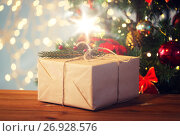 Купить «close up of christmas gift with fir brunch», фото № 26928576, снято 7 октября 2015 г. (c) Syda Productions / Фотобанк Лори