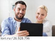 Купить «smiling happy couple with tablet pc at home», фото № 26928796, снято 11 февраля 2017 г. (c) Syda Productions / Фотобанк Лори