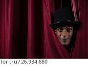 Купить «Ballet dancer peeking through a stage curtain», фото № 26934880, снято 20 апреля 2017 г. (c) Wavebreak Media / Фотобанк Лори