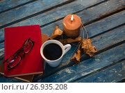 Купить «High angle view of tea cup with eyeglasses and books by illuminated candle», фото № 26935208, снято 11 апреля 2017 г. (c) Wavebreak Media / Фотобанк Лори