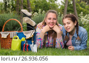 Купить «smiling young woman and girl with gardening tools in outdoors», фото № 26936056, снято 18 апреля 2017 г. (c) Яков Филимонов / Фотобанк Лори