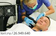 Купить «Woman doctor is doing vacuum massage procedure on face of adult client in clinic.», видеоролик № 26949640, снято 23 августа 2017 г. (c) Яков Филимонов / Фотобанк Лори