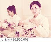 Купить «Female manicurist showing lacquer color schemes», фото № 26950608, снято 2 февраля 2017 г. (c) Яков Филимонов / Фотобанк Лори