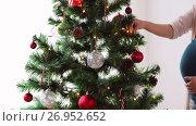 Купить «pregnant woman decorating christmas tree at home», видеоролик № 26952652, снято 14 сентября 2017 г. (c) Syda Productions / Фотобанк Лори