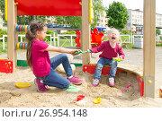 Купить «Ссора в песочнице. Большая девочка отнимает игрушку у младшей сестры. Маленькая девочка плачет», фото № 26954148, снято 30 июня 2017 г. (c) Лариса Капусткина / Фотобанк Лори