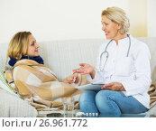 Купить «Mature doctor questioning young blonde with flu at home», фото № 26961772, снято 23 марта 2019 г. (c) Яков Филимонов / Фотобанк Лори