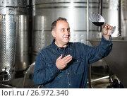 Купить «Worker of winery costs with glass of red wine near tanks», фото № 26972340, снято 12 октября 2016 г. (c) Яков Филимонов / Фотобанк Лори