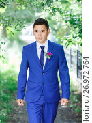 Male model, the groom portrait in a blue suit with a boutonniere among the green foliage on a wedding day. Стоковое фото, фотограф Евгений Майнагашев / Фотобанк Лори